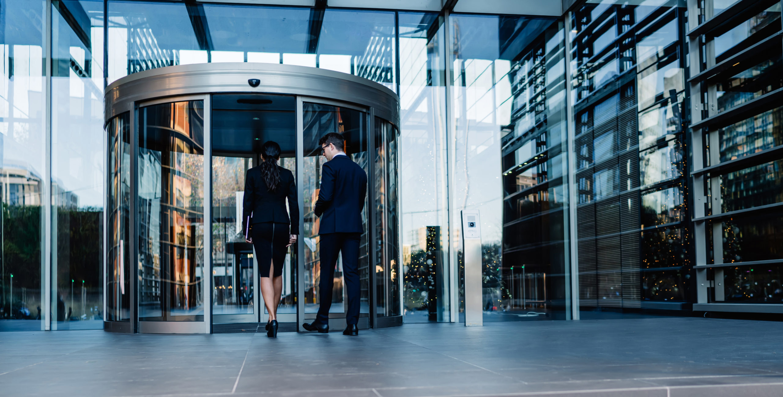 Back view of elegant man and woman walking into round revolving doors while entering contemporary glass skyscraper building of corporation office